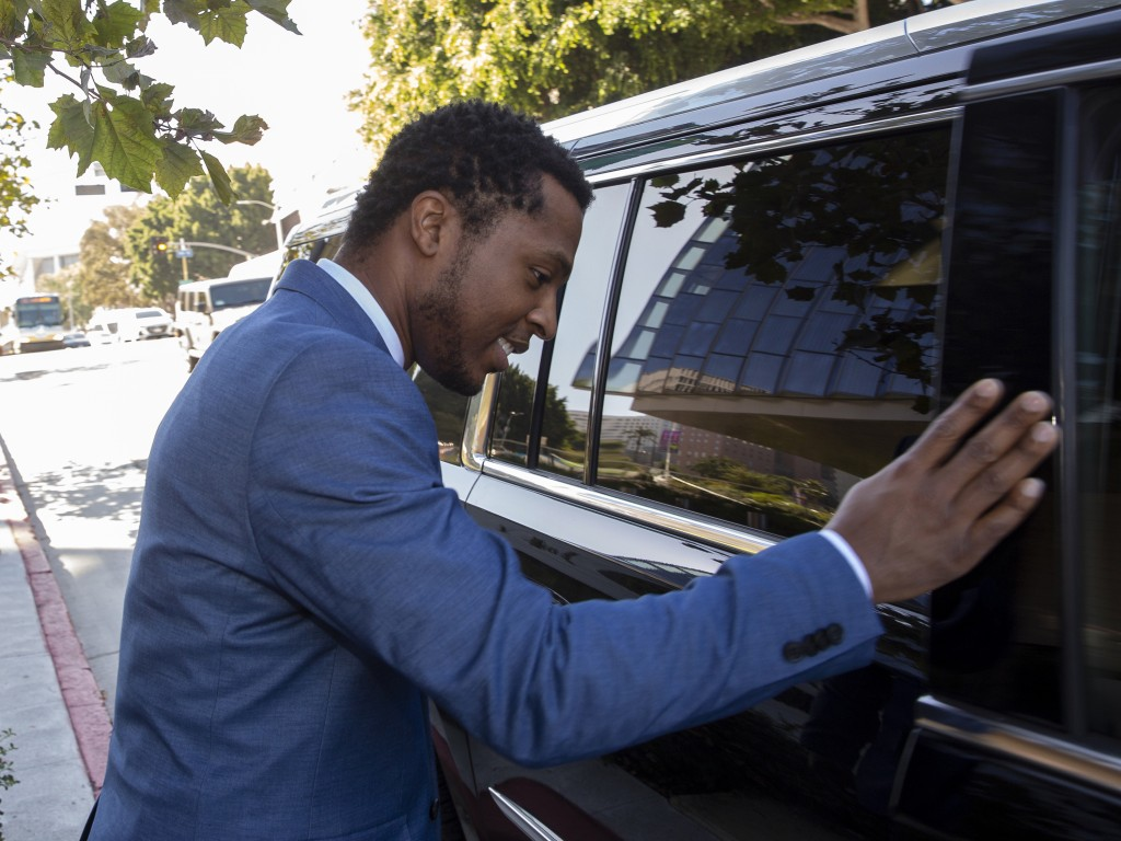 Rapper Marcus Gray avoids talking to the media as he rushes into a waiting SUV, outside the federal courthouse in Los Angeles, Thursday, Aug. 1, 2019....