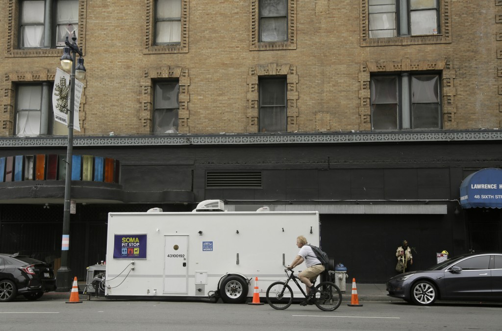 "A man rides his bicycle past a ""Pit Stop"" public toilet on Sixth Street, Thursday, Aug. 1, 2019, in San Francisco. A 5-year-old portable toilet progra..."
