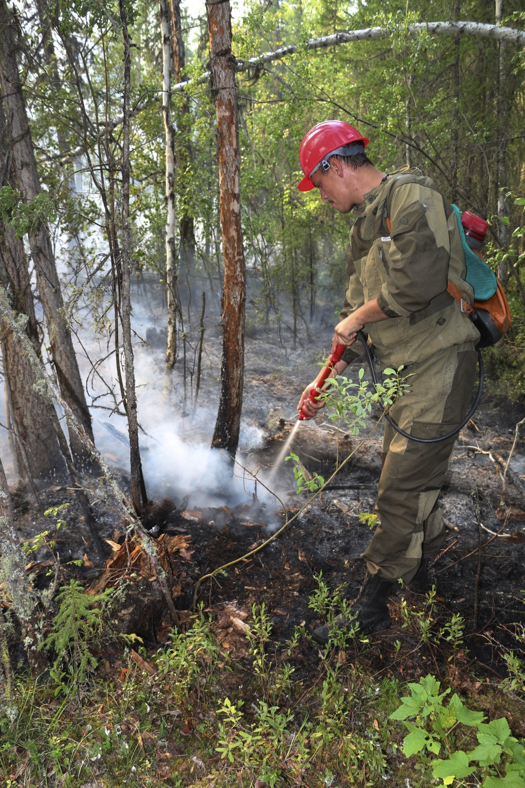 This photo taken on Monday, July 29, 2019 and released by Press Service of the Ministry of Forestry of the Krasnoyarsk Territory, shows a firefighter ...