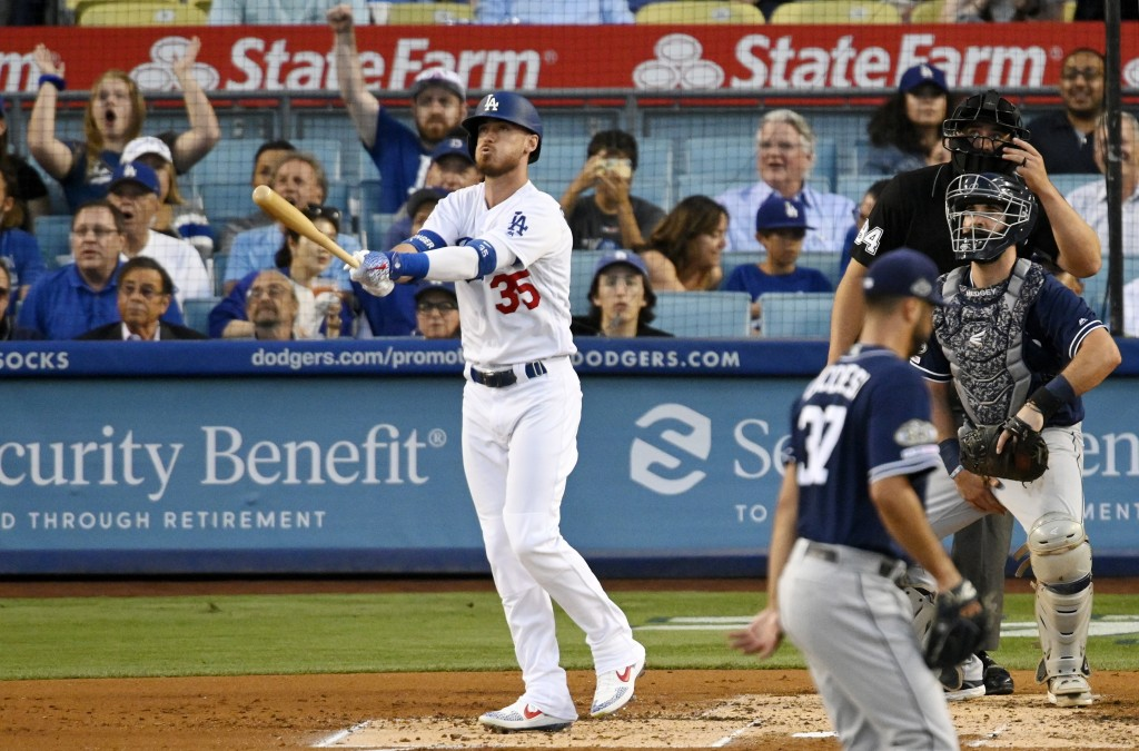 Los Angeles Dodgers' Cody Bellinger, left, heads to first on a solo home run off San Diego Padres' Joey Lucchesi, who walks off the mound, while catch...