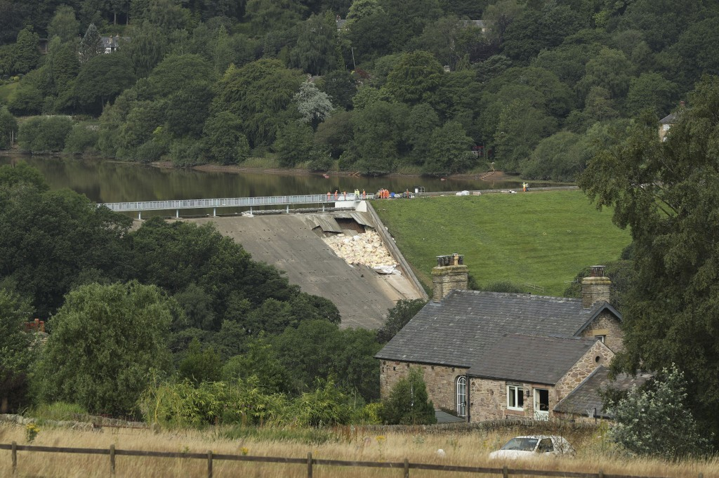 A view of the damaged Toddbrook Reservoir near the village of Whaley Bridge,in Derbyshire, England, Saturday, Aug. 3, 2019. Emergency workers are raci