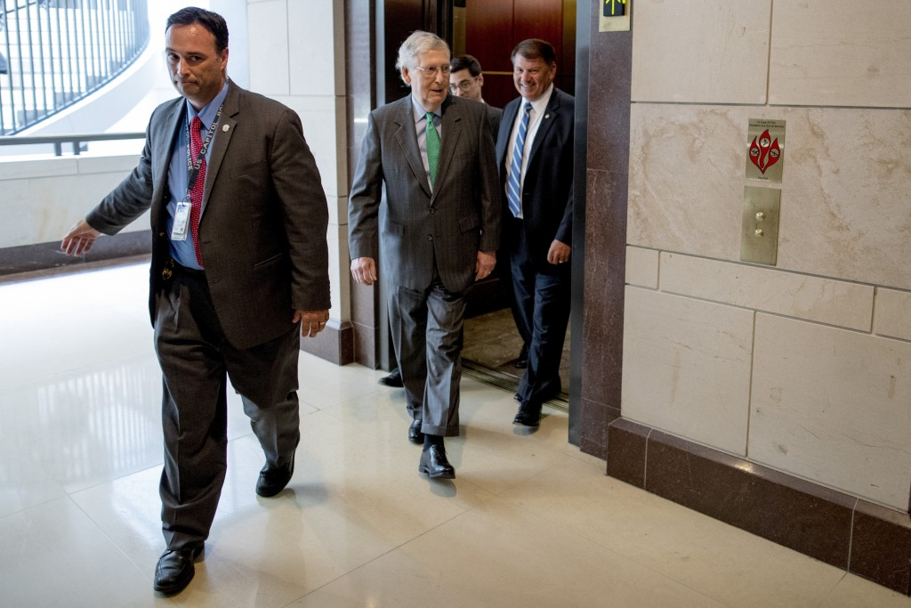 FILE - In this July 10, 2019, file photo, Senate Majority Leader Mitch McConnell of Ky., center, and Sen. Mike Rounds, R-S.D., right, arrive for a clo