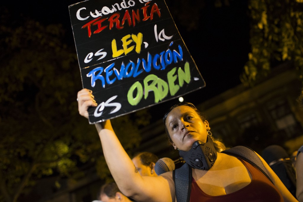 """A woman holds a sign with message that reads in Spanish: """"When tyranny is the law, a revolution is in order"""" during a protest outside the governor's r"""