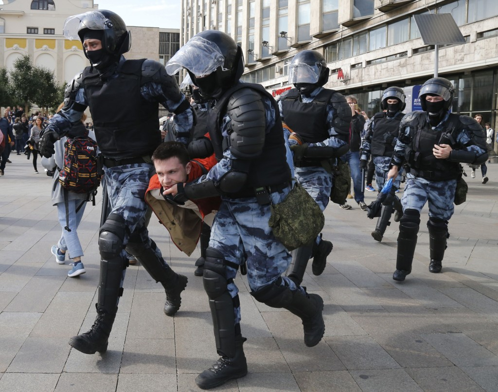 Police officers detain a protestor, during an unsanctioned rally in the center of Moscow, Russia, Saturday, Aug. 3, 2019. Moscow police on Saturday de...