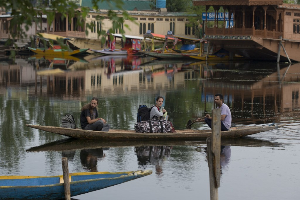Foreign tourist cross the Dal Lake on a shikara as they prepare to leave Srinagar, Indian controlled Kashmir, Saturday, Aug. 3, 2019. A government ord...