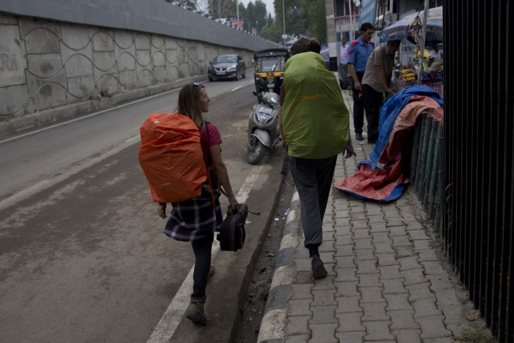 Belgians tourists walks towards a taxi stand as they prepare to leave Srinagar, Indian controlled Kashmir, Saturday, Aug. 3, 2019. A government order