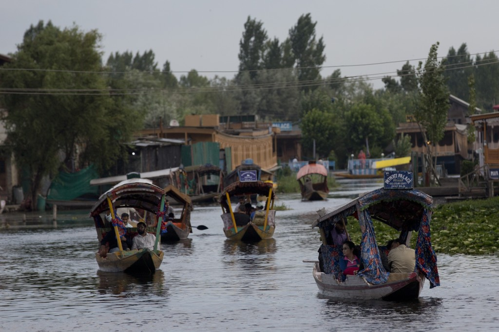 Tourists in Shikaras, a traditional gondola, cross the Dal Lake as they prepare to leave Srinagar, Indian controlled Kashmir, Saturday, Aug. 3, 2019. ...