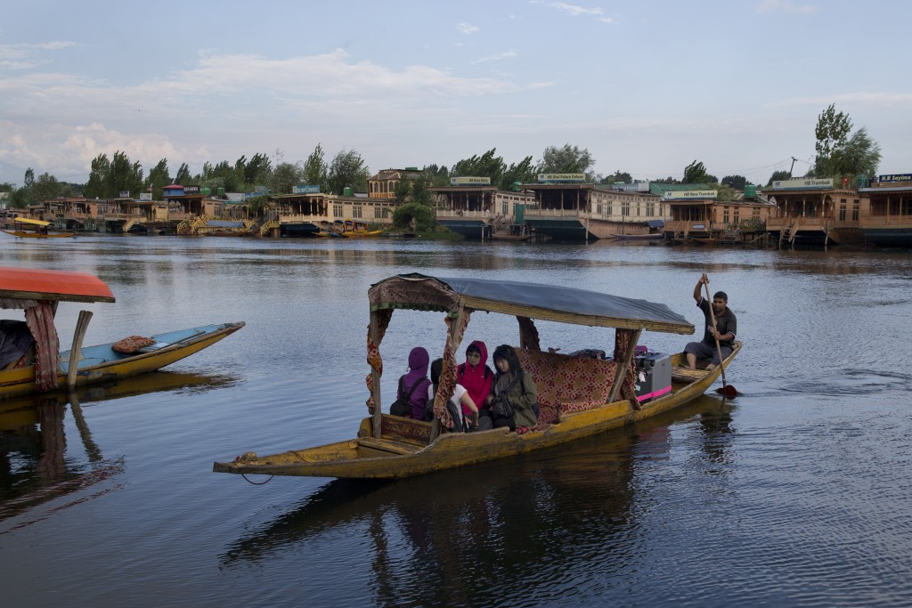 Foreign tourists cross the Dal Lake on a Shikara as they prepare to leave Srinagar, Indian controlled Kashmir, Saturday, Aug. 3, 2019. A government or