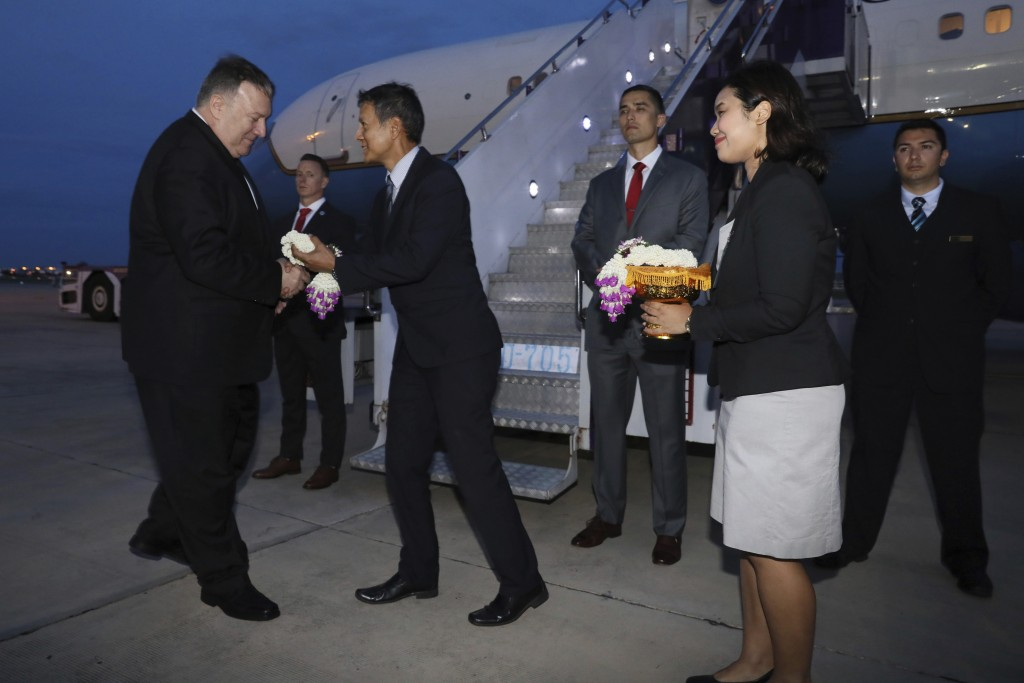 U.S. Secretary of State Mike Pompeo is presented with flowers as he boards his plane to depart for Australia from Don Mueang International Airport, in...