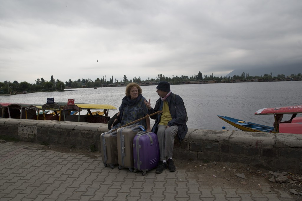 An Italian couple wait for their taxi as they prepare to leave Srinagar, Indian controlled Kashmir, Saturday, Aug. 3, 2019. A government order in Indi...