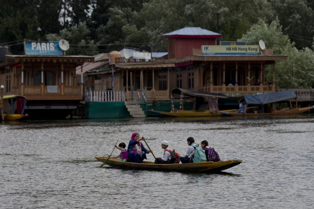 A Kashmiri woman rows children to school on a shikara, a traditional gondola, on Dal Lake in Srinagar, Indian controlled Kashmir, Saturday, Aug. 3, 20...