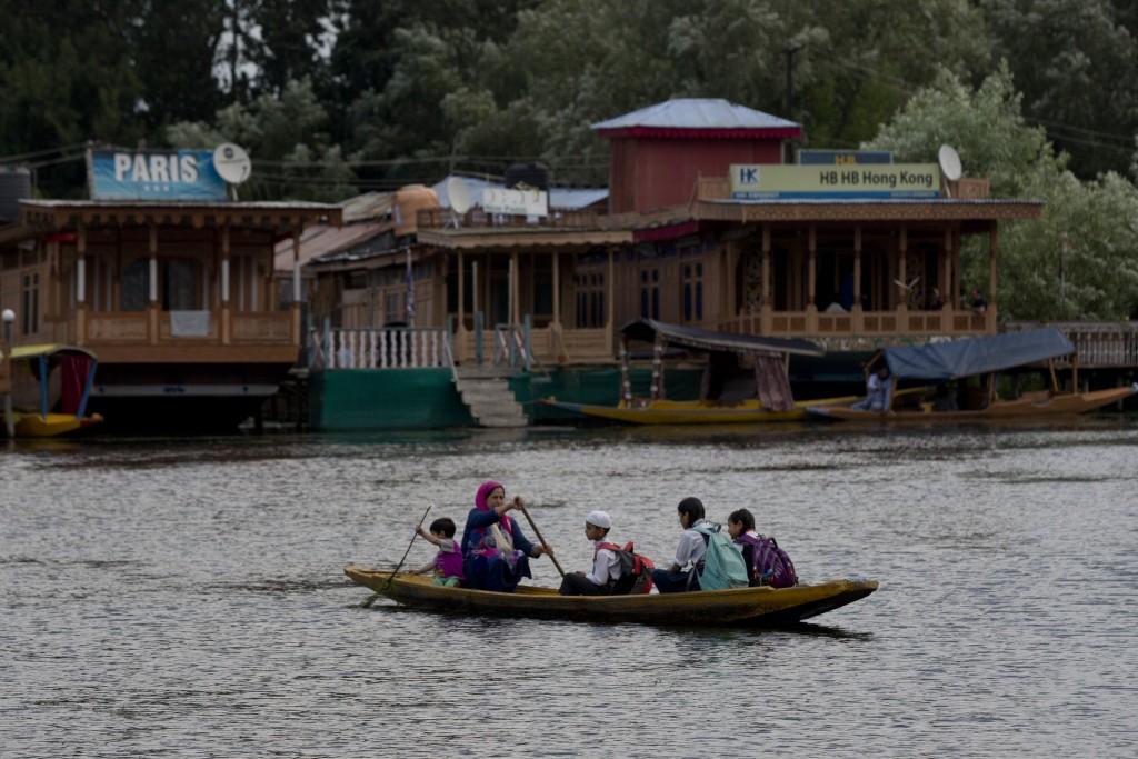 A Kashmiri woman rows children to school on a shikara, a traditional gondola, on Dal Lake in Srinagar, Indian controlled Kashmir, Saturday, Aug. 3, 20