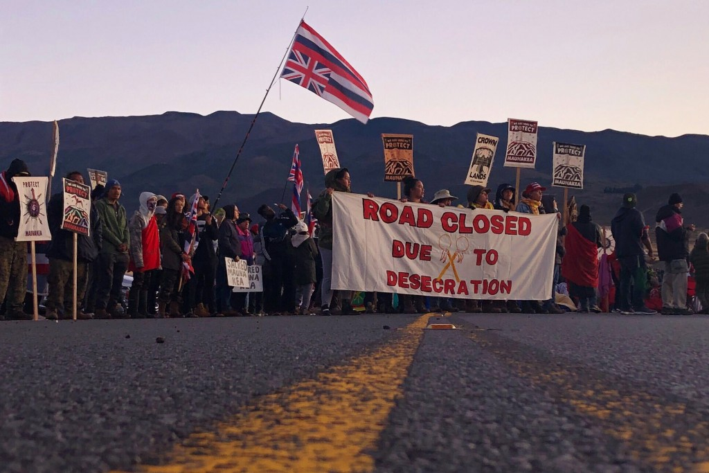 FILE - In this July 15, 2019, file photo, demonstrators block a road at the base of Hawaii's tallest mountain, in Mauna Kea, Hawaii, to protest the co...