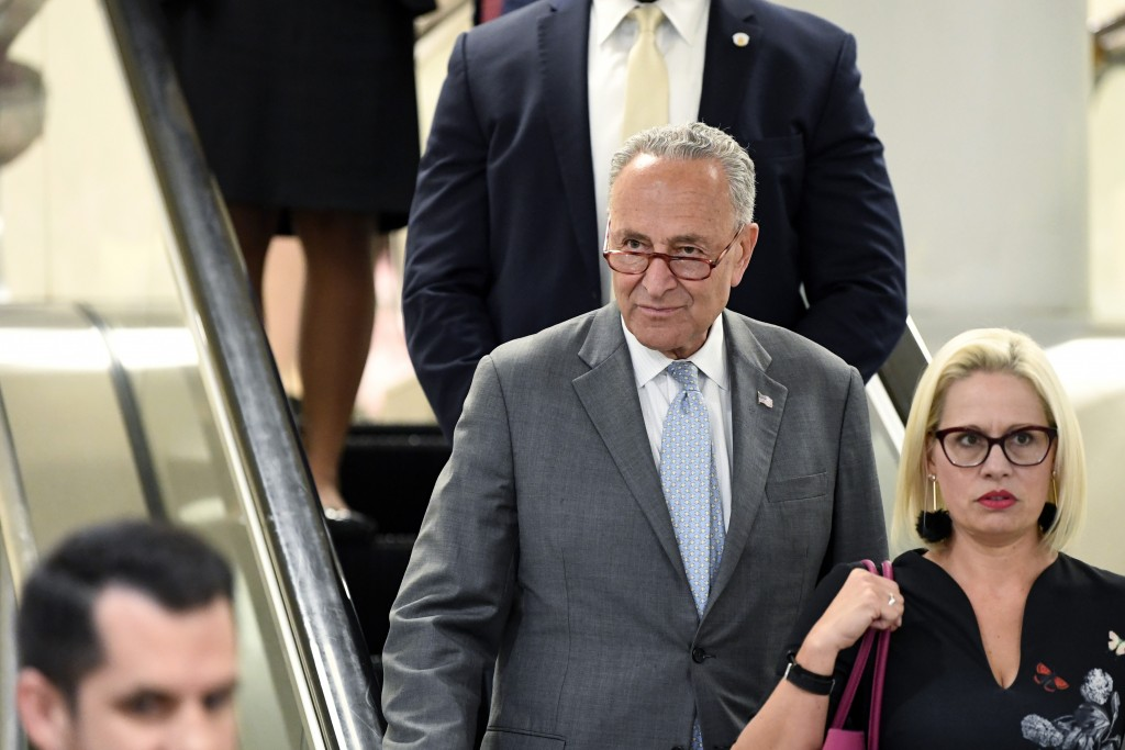 FILE - In this July 10, 2019, file photo, Senate Minority Leader Sen. Chuck Schumer of N.Y., rides the escalator on Capitol Hill in Washington, as he