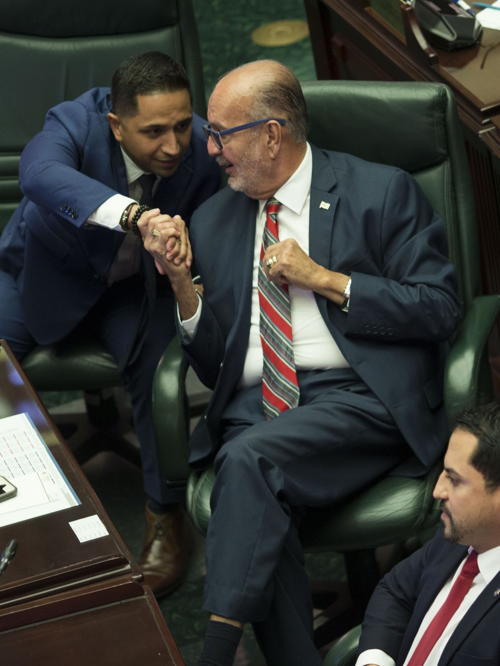 """Luis """"Junior"""" Perez, center, shakes hands with fellow lawmakers Urayoan Hernandez as members of Puerto Rico's House of Representatives celebrate their..."""