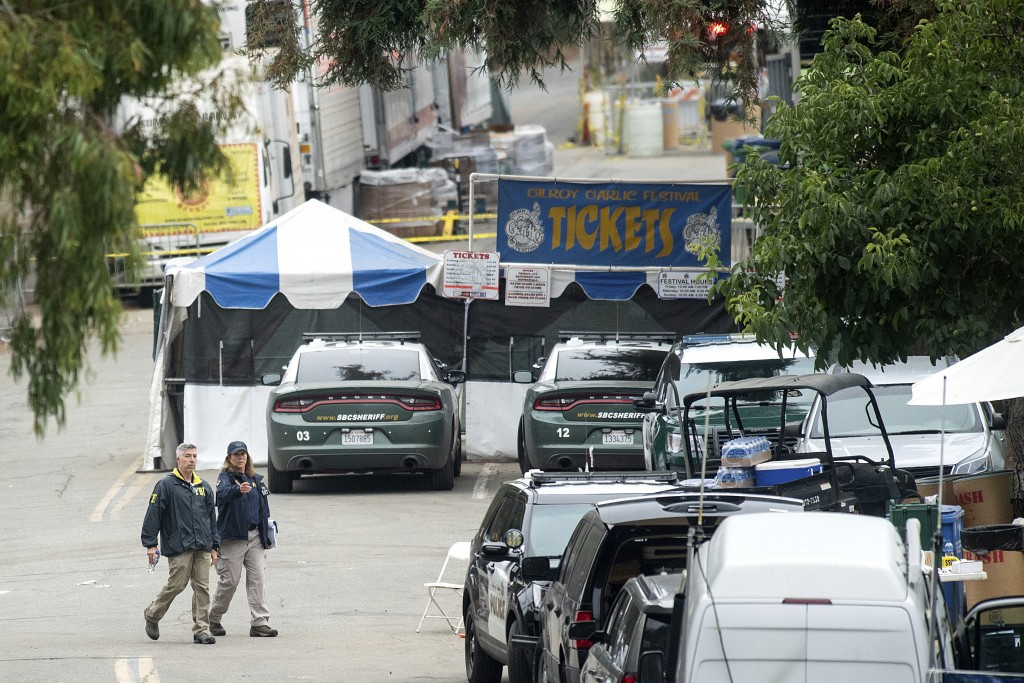 FILE - In this July 29, 2019 file photo FBI personnel pass a ticket booth at the Gilroy Garlic Festival in Calif., the morning after a gunman killed m...