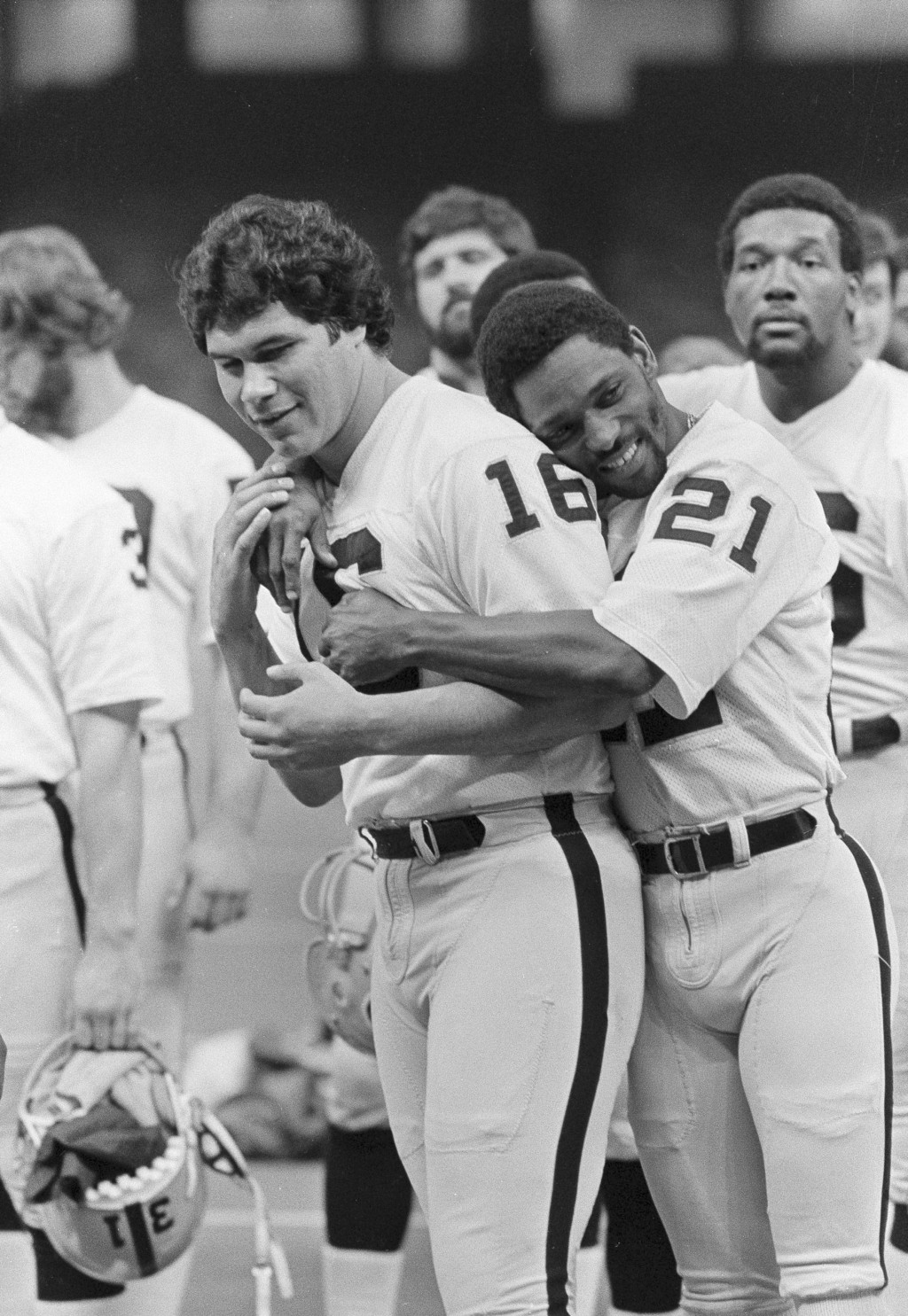 FILE - In this Jan. 21, 1981, file photo Oakland Raiders wide receiver Cliff Branch (21) hugs quarterback Jim Plunkett (16) as the Raiders lined up fo
