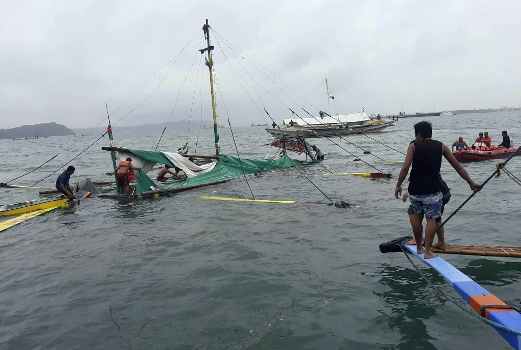 In this photo provided by the Philippine Red Cross, rescuers checks the remains of a ferry boat after it capsized due to bad weather in the waters bet