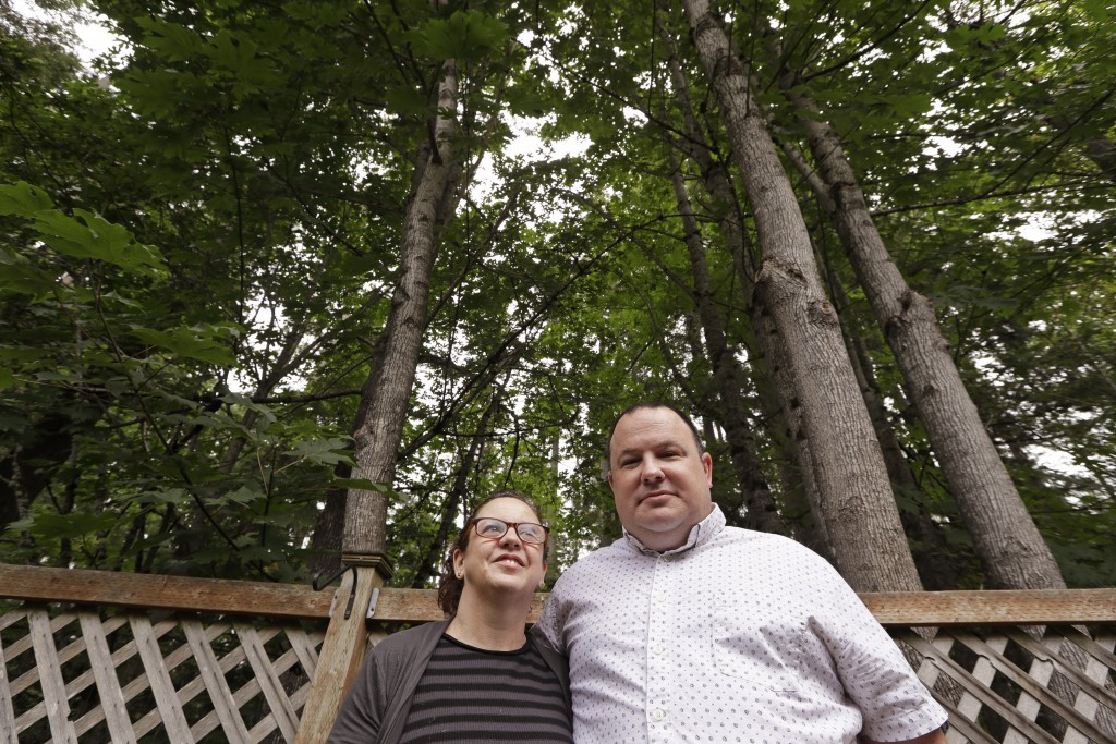 In this photo taken Friday, Aug. 2, 2019, Amy and Jason Ritchie stand in the backyard of their home, adjacent to a forest of conifer and deciduous tre
