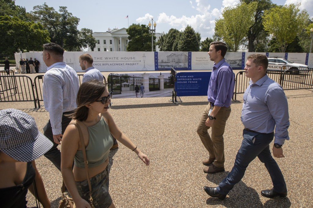 Visitors and office workers from nearby walk in front of the White House in Washington with the newly installed added fence for construction work, Thu