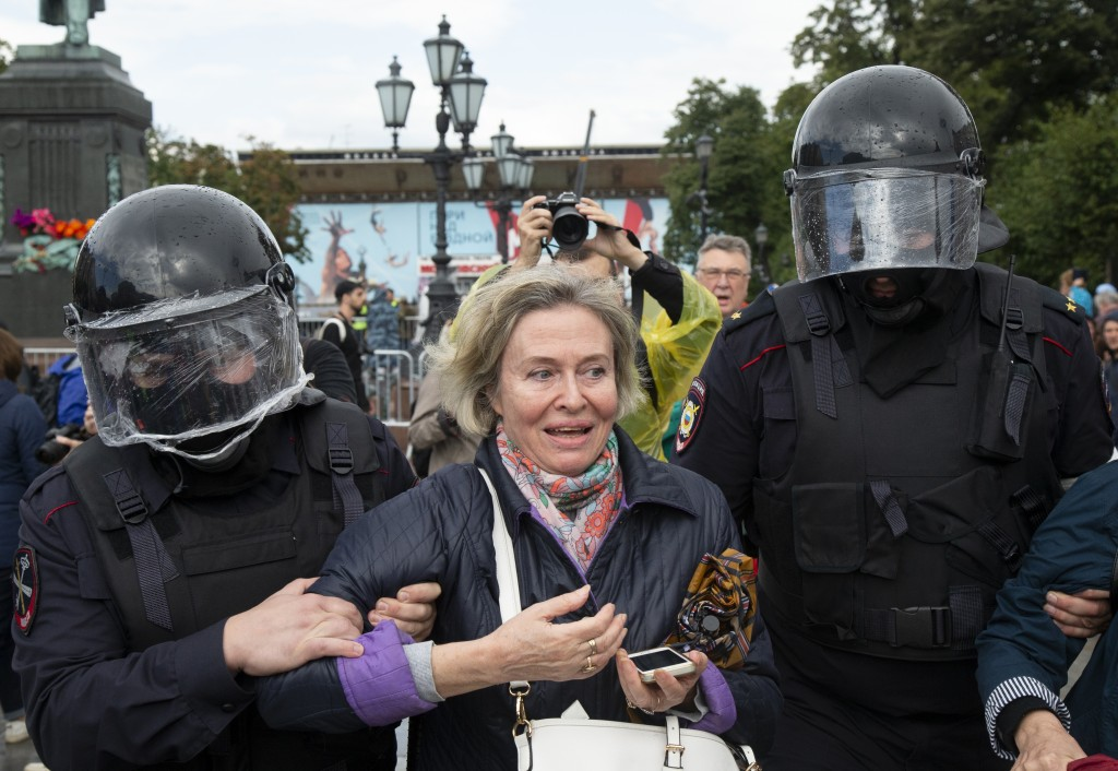 Police officers detain a woman during an unsanctioned rally in the center of Moscow, Russia, Saturday, Aug. 3, 2019. Moscow police detained more than