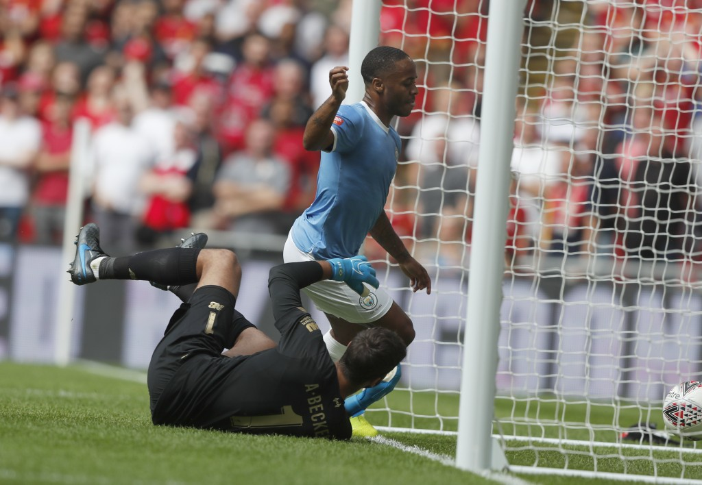 Manchester City's Raheem Sterling celebrates after scoring his sides 1st goal as Liverpool's goalkeeper Alisson Becker looks at the ball in the back o...