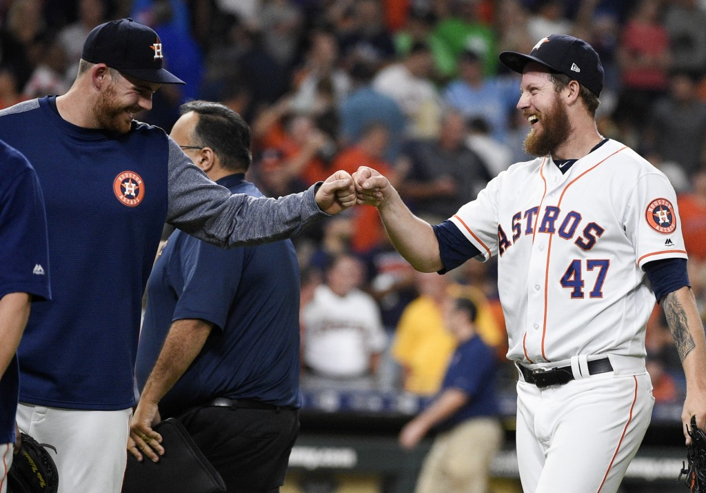 Houston Astros relief pitcher Chris Devenski, right, celebrates with Joe Biagini, who had pitched the eighth inning, the team's win and four-pitcher c
