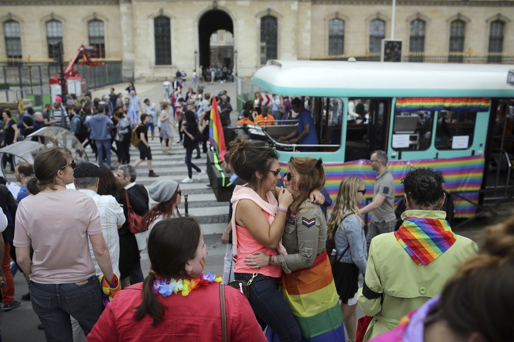 FILE - In this Saturday, July 2, 2016 file photo people hug during the annual Gay Pride march in Paris, France. Single women and lesbians in France wo
