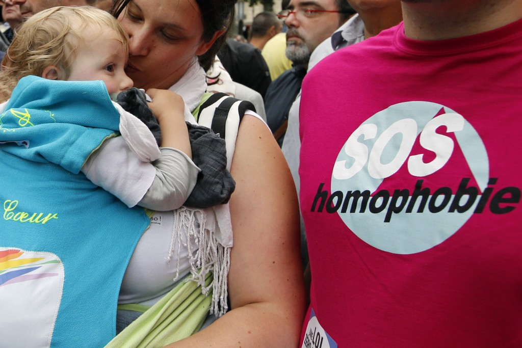 """FILE - In this Saturday, June 28, 2014 file photo a woman kisses a baby next to a man wearing a shirt reading """"SOS Homophobia"""" during the annual Gay P"""