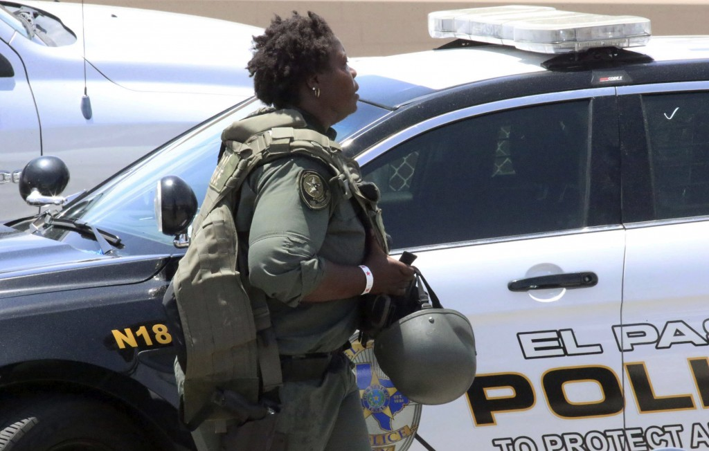 A law enforcement officer walks near the scene of a shooting at a shopping mall in El Paso, Texas, on Saturday, Aug. 3, 2019.   Multiple people were k...