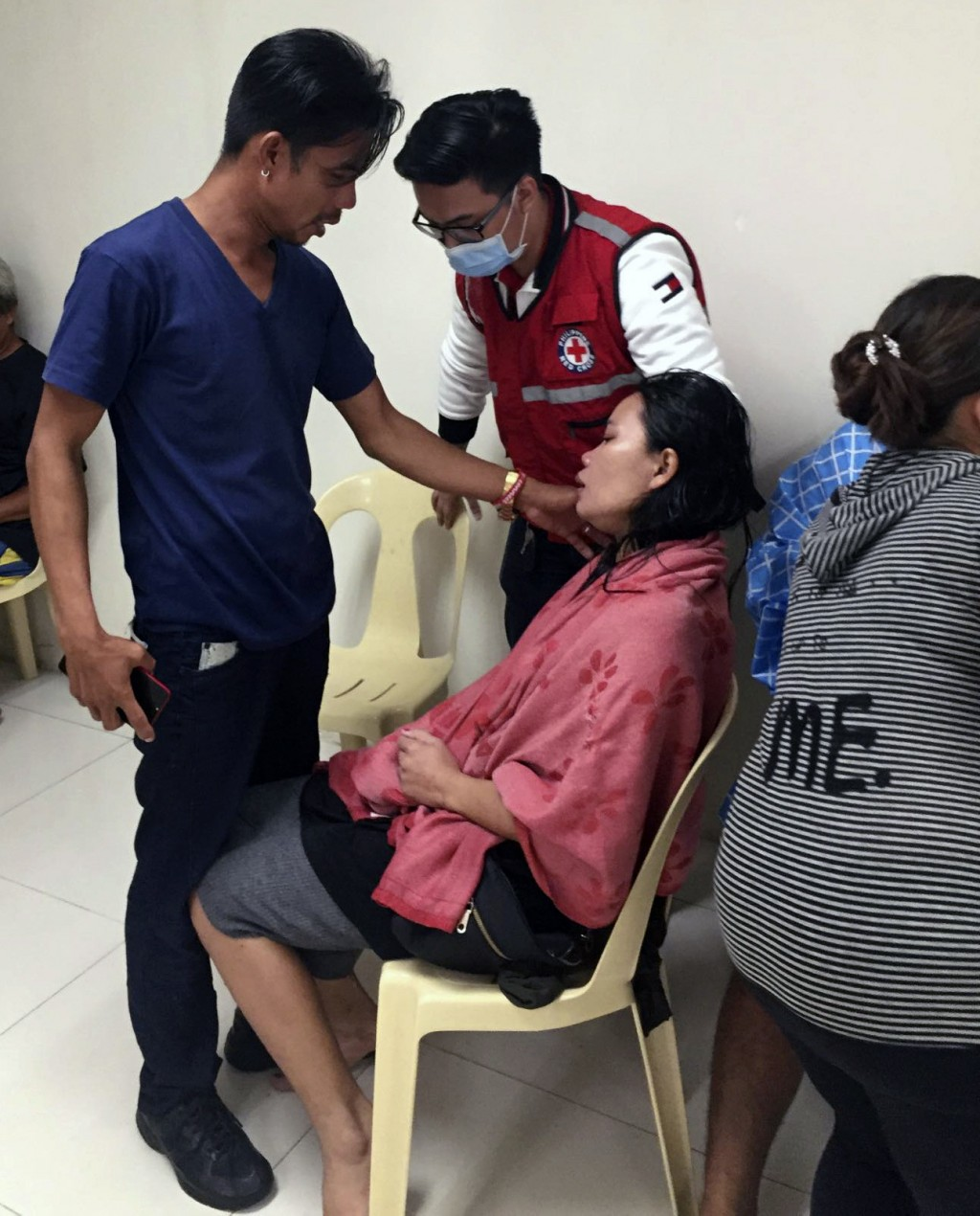In this photo provided by the Philippine Red Cross, a survivor takes a rest after their ferry boat capsized due to bad weather in the waters between G...