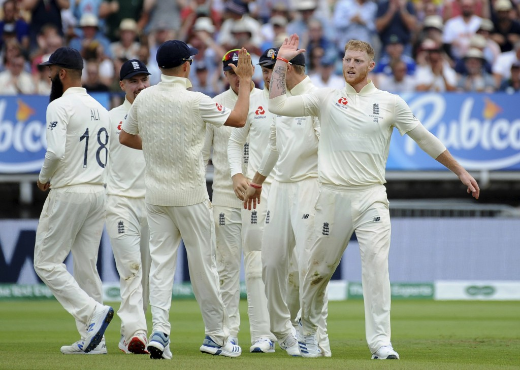 England's Ben Stokes, right, celebrates with teammates after dismissing Australia's Travis Head during day four of the first Ashes Test cricket match ...