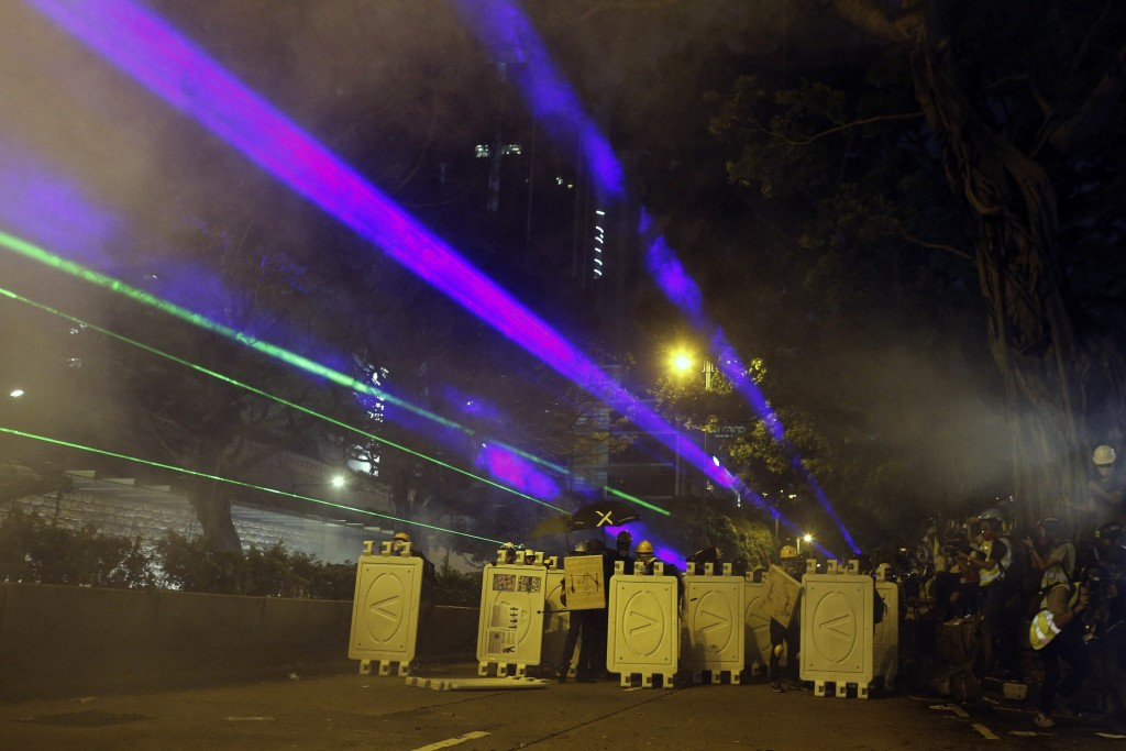 Protesters huddle behind barriers and use laser beams to shine at riot police during confrontation in Tsim Sha Tsui in Hong Kong on Saturday, Aug. 3, ...