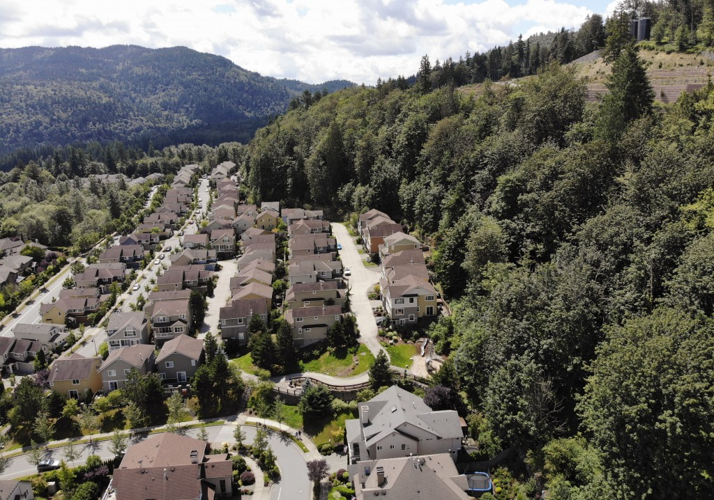 In this photo taken July 24, 2019, houses stand adjacent to a forest in the Seattle suburb of Issaquah, Wash. Experts say global warming is changing t...