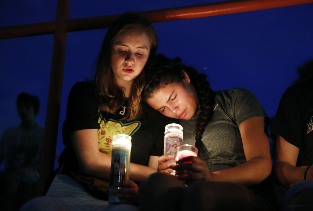 Melody Stout and Hannah Payan comfort each other during a vigil for victims of the shooting that occurred earlier in the day at a shopping center, Sat