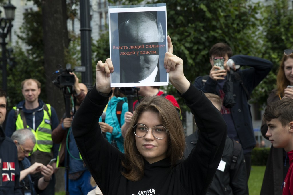 """A woman holds a poster with a portrait of Russian President Vladimir Putin and words reading """"The power of people is stronger than the people in power..."""