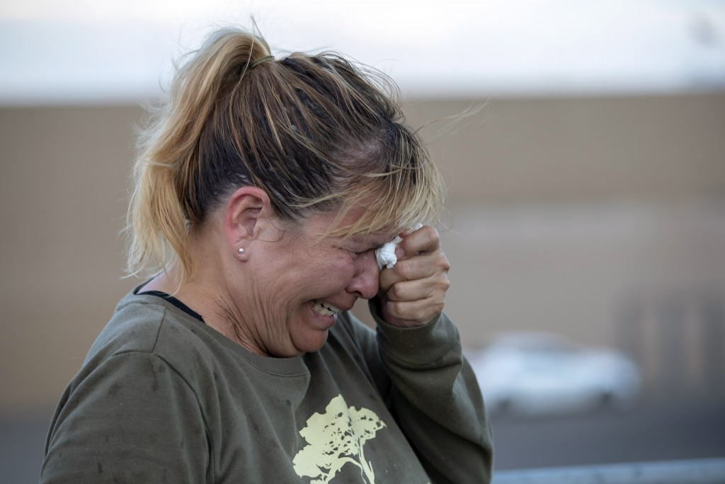 Edie Hallberg cries while speaking to police outside a Walmart store where a shooting occurred earlier in the day as she looks for her missing mother ...
