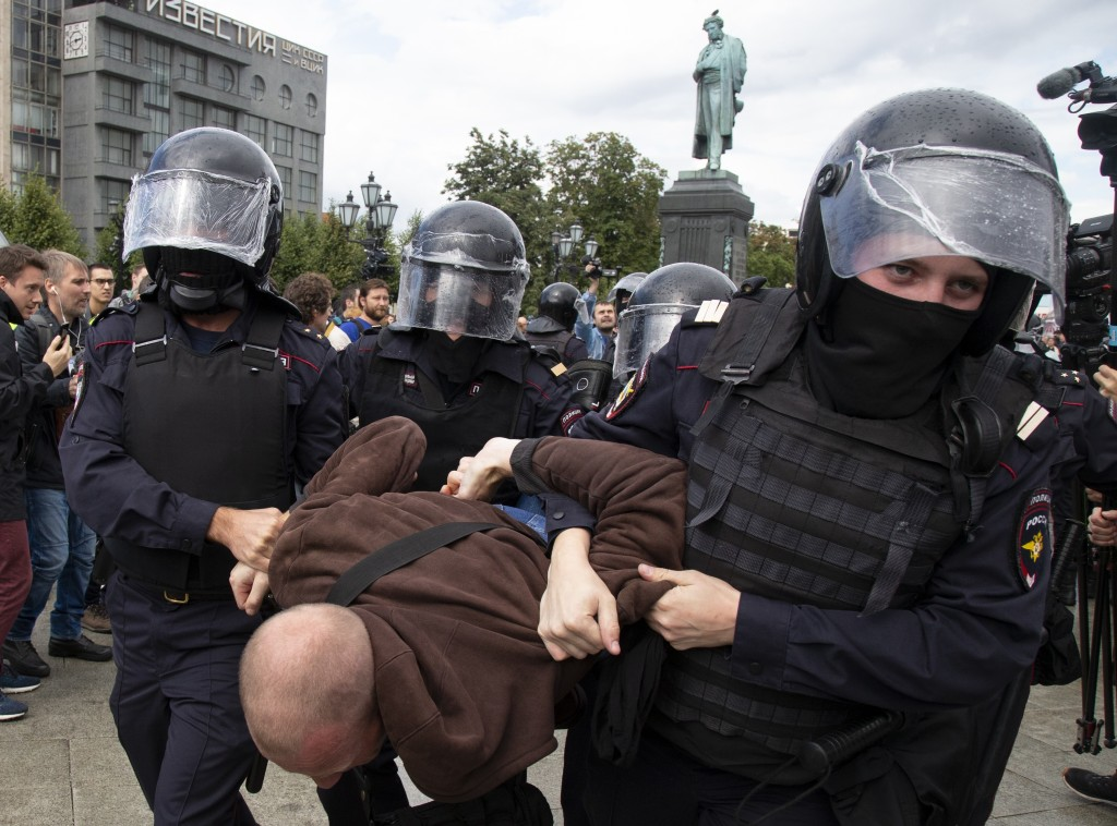 Police officers detain a protestor, during an unsanctioned rally in Pushkin Square in Moscow, Russia, Saturday, Aug. 3, 2019. Moscow police detained m...