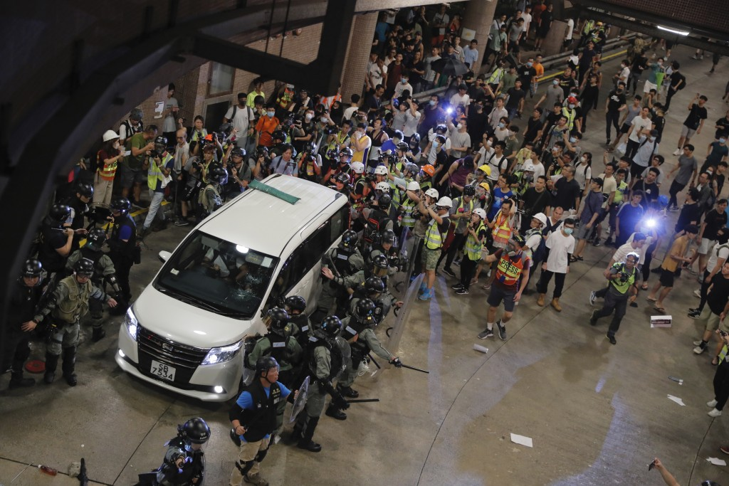 Police protect a police vehicle in Wong Tai Sin district in Hong Kong on Saturday, Aug. 3, 2019. Protesters and authorities clashed in Hong Kong again
