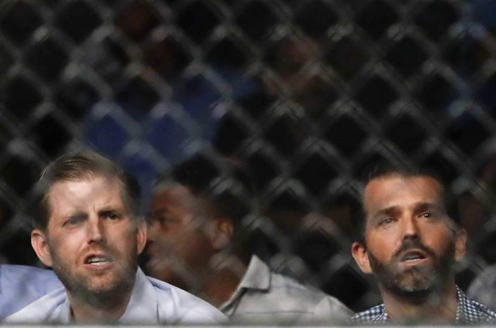 Eric Trump, left, and Donald Trump Jr. watch during the second round of a welterweight mixed martial arts bout between Robbie Lawler and Colby Covingt