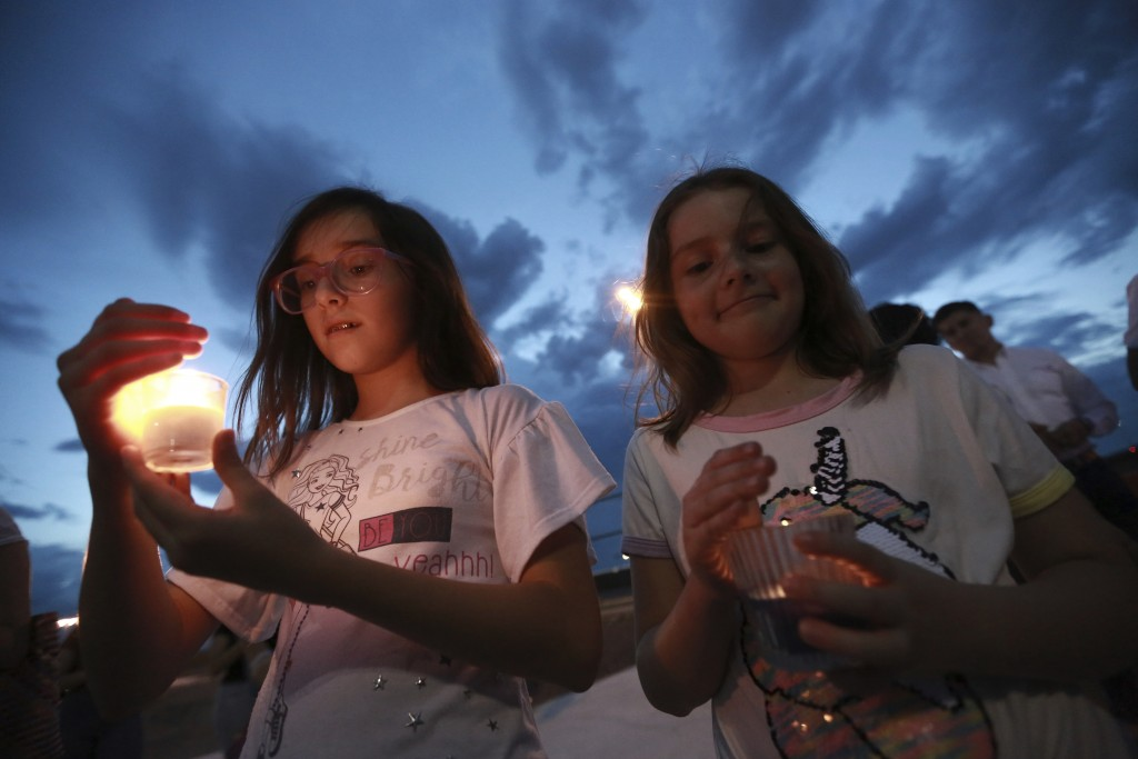 People gather in Juarez, Mexico, Saturday, Aug. 3, 2019, in a vigil for the 3 Mexican nationals who were killed in an El Paso shopping-complex shootin