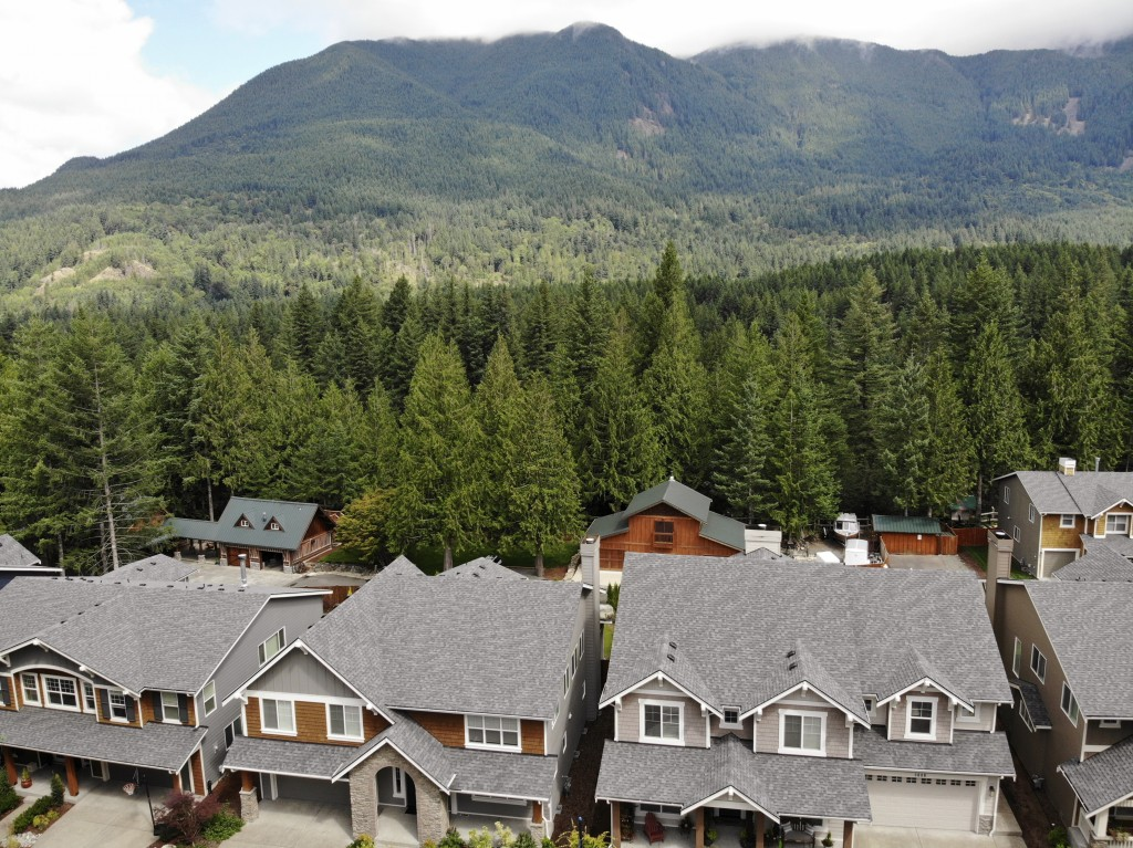 In this photo taken July 24, 2019, houses are backed up to a forest in the Cascade foothills of North Bend, Wash. Experts say global warming is changi...