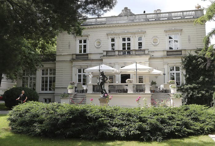 In this photo taken on Friday July 12, 2019, a man works in the garden of a high-end restaurant, Amber Room, where top Polish politicians and business