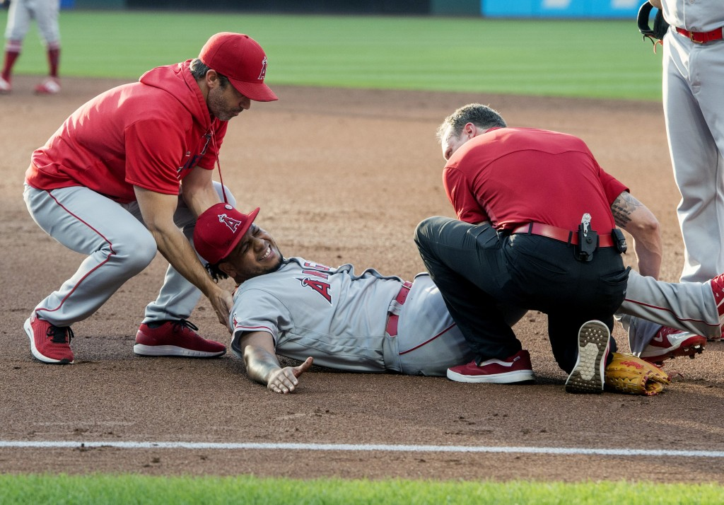 Los Angeles Angels starting pitcher Felix Pena, center, is tended to by trainers after an injury while covering first base during the second inning of
