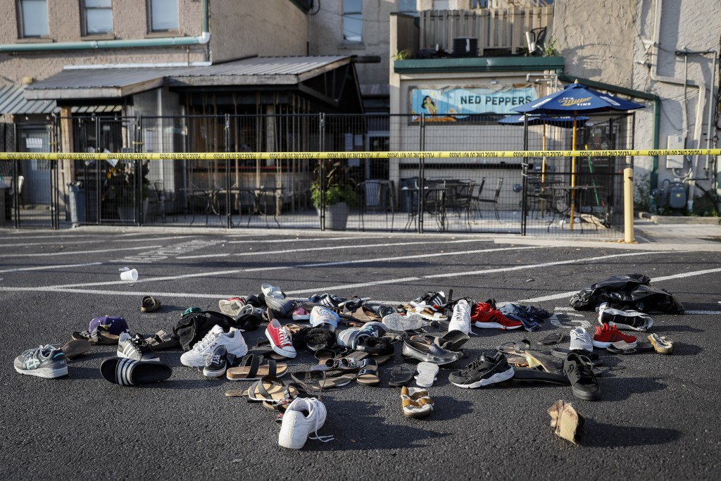 Shoes are piled outside the scene of a mass shooting including Ned Peppers bar, Sunday, Aug. 4, 2019, in Dayton, Ohio. Several people in Ohio have bee