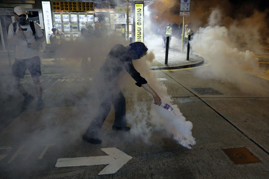 A protester pours water on a tear gas canister during a confrontation with police in Hong Kong on Saturday, Aug. 3, 2019. Hong Kong protesters removed...