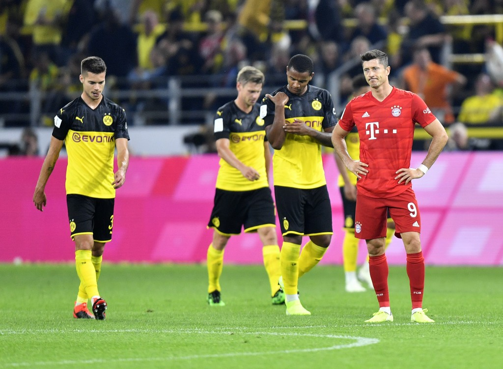 Bayern's Robert Lewandowski, right, reacts after Dortmund's Jadon Sancho scoring his side's second goal during the German Supercup final soccer match ...