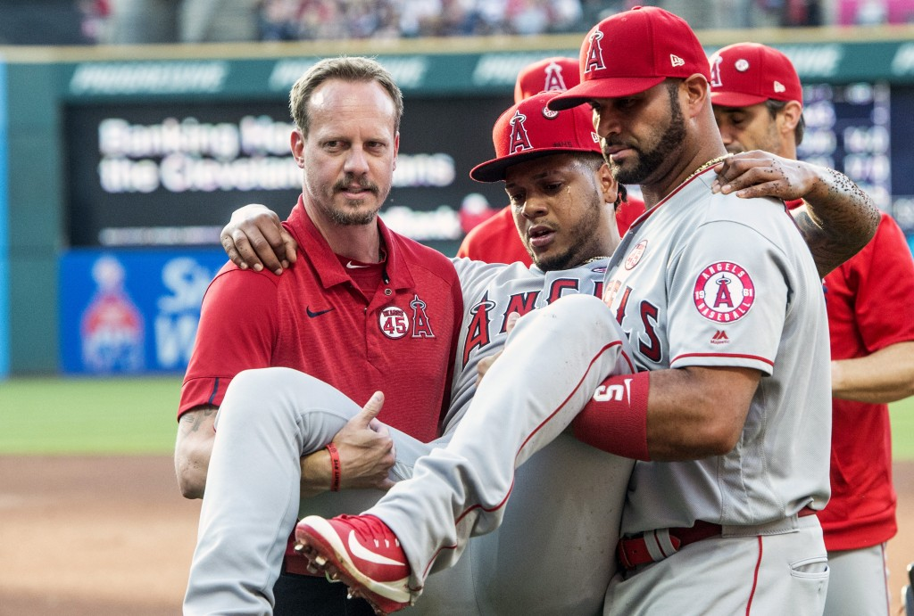 Los Angeles Angels starting pitcher Felix Pena is carried off the field by teammate Albert Pujols and an unidentified trainer during the second inning...