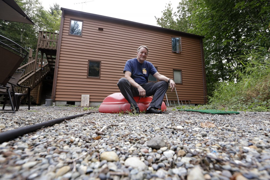 In this photo taken Friday, Aug. 2, 2019, Wayne Elson poses for a photo in the backyard of his home, where gravel beds and landscaping kept green help