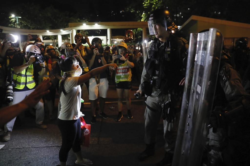 A woman shouts at a police officer in Wong Tai Sin district in Hong Kong during the early hours of Sunday, Aug. 4, 2019. Protesters and authorities cl...
